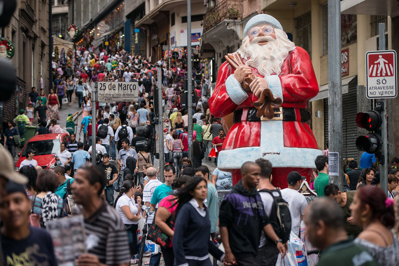 """. People walk past a statue of Santa Claus placed at \""""25 de Marco\"""" road in Sao Paulo, Brazil, on December 15, 2012. The road 25 de Marco is known as the busiest shopping street, with retailers and wholesalers. YASUYOSHI CHIBA/AFP/Getty Images"""