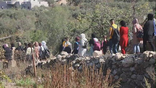 """Palestinians participate in a march to explore the """"al-Hawiyah"""" water spring in the village of Hussan"""