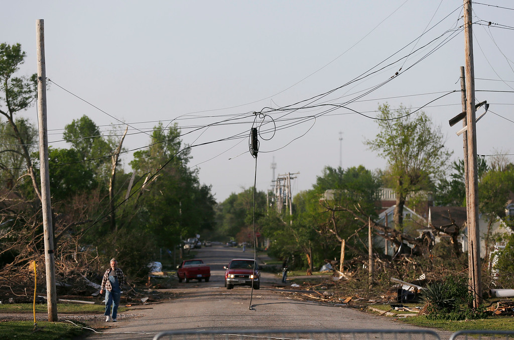 . A resident walks under damaged power lines after a tornado in Baxter Springs, Kan., Monday, April 28, 2014. Sunday\'s tornado injured 25 people and damaged dozens of buildings. (AP Photo/Orlin Wagner)