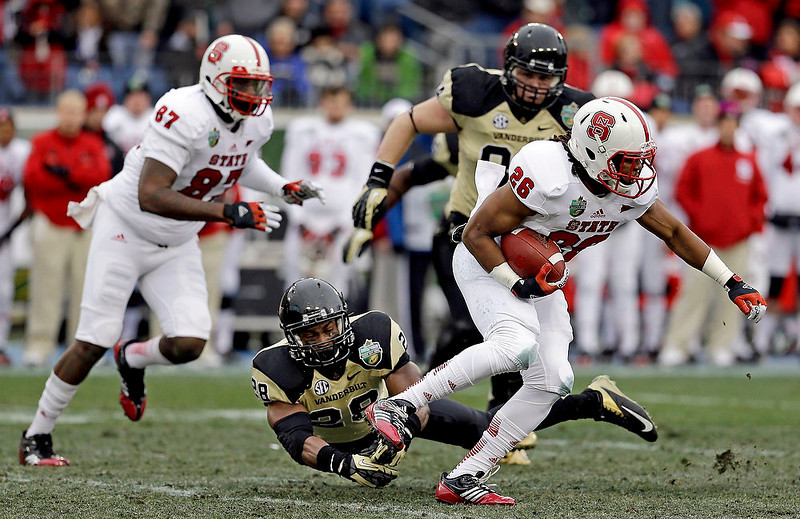 . North Carolina State running back Tony Creecy (26) breaks away from Vanderbilt safety Karl Butler (28) in the first quarter of the Music City Bowl NCAA college football game, Monday, Dec. 31, 2012, in Nashville, Tenn. At rear are North Carolina State tight end Mario Carter (87) and Vanderbilt defensive tackle Rob Lohr (84). (AP Photo/Mark Humphrey)