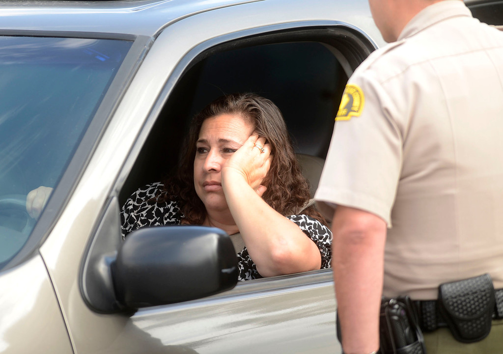 . A woman reacts to the news that she cannot return home as San Bernardino County Sheriff\'s Deputies and Rialto Police officers search for pursuit suspects along the 100 block of East Meadow Lane in Rialto April 16, 2013.   GABRIEL LUIS ACOSTA/STAFF PHOTOGRAPHER.