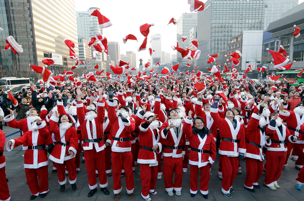 . More than 1,000 volunteers clad in Santa Claus costumes throw their hats in the air as they gather to deliver gifts for the poor in downtown Seoul, South Korea, Tuesday, Dec. 24, 2013. (AP Photo/Lee Jin-man)