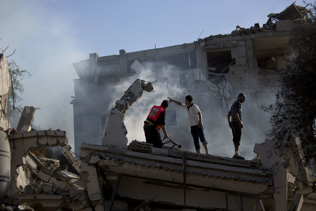 . Palestinian firefighters and residents try to extinguish fire at a house destroyed by an overnight Israeli air strike, on July 16, 2014, in Gaza City. New Israeli air and tank strikes in Gaza early today killed several people, medics said, bringing the death toll from Israel\'s operation in the besieged Palestinian territory to 204. AFP PHOTO / MAHMUD HAMS/AFP/Getty Images