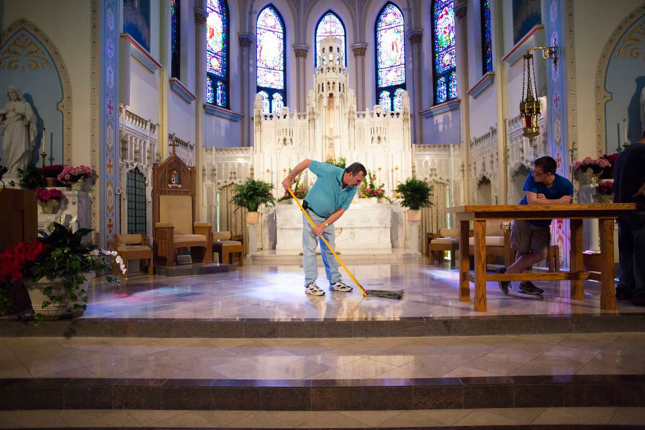 Mike Hinkle mops the floor where the altar once was. Josh Hinkle (son) looks on.