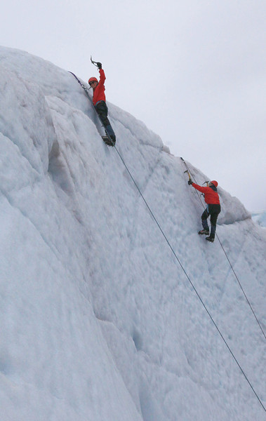 Stephanie raising her ice pick at the top of the climb