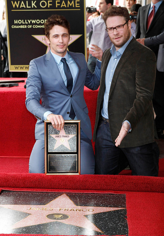 . Actor James Franco (L) poses with his newly unveiled star on the Hollywood Walk of Fame, with actor Seth Rogen March 7, 2013. REUTERS/Fred Prouser