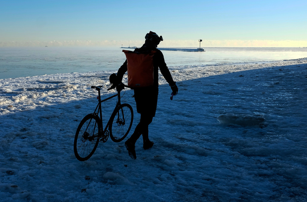 . A bike commuter walks on the ice covered path along the shore of Lake Michigan, Monday, Dec. 19, 2016, in downtown Chicago. Lingering arctic air and wind also has combined for dangerous subzero wind chills, though the National Weather Service forecast calls for temperatures to warm into the upper teens and twenties during the day. (AP Photo/Kiichiro Sato)
