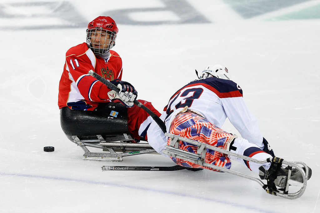 . Rico Roman of USA (R) collides with Alexey Amosov during the Ice Sledge Hockey Gold Medal match between Russia and USA at the Shayba Arena during day eight of the 2014 Paralympic Winter Games on March 15, 2014 in Sochi, Russia.  (Photo by Harry Engels/Getty Images)