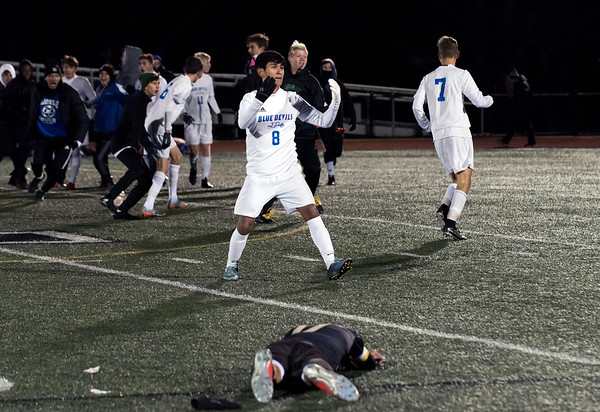 11/14/18 Wesley Bunnell | Staff Plainville #23 vs Stonington #3 soccer in the Class M Semifinal at Xavier High School on Wednesday night. Michael Torres (8) celebrates with teammates as a dejected Stonington player lies on the turf.