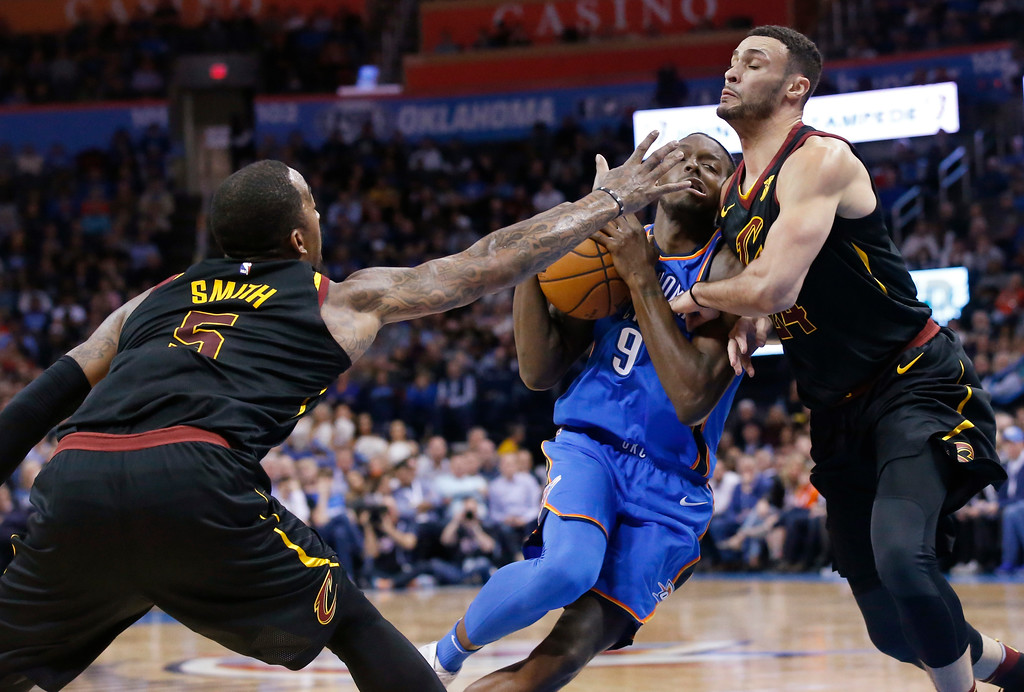 . Oklahoma City Thunder forward Jerami Grant (9) drives between Cleveland Cavaliers guard J.R. Smith (5) and forward Larry Nance Jr. (24) during the second half of an NBA basketball game in Oklahoma City, Tuesday, Feb. 13, 2018. (AP Photo/Sue Ogrocki)