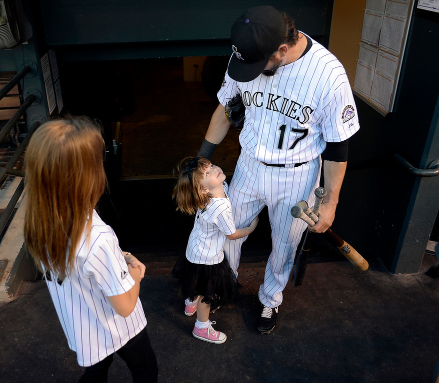 . Todd Helton\'s youngest daughter Gentry Grace hugs her dad\'s leg before the start of action in Denver. The Colorado Rockies hosted the Boston Red Sox and said farewell to longtime first baseman Todd Helton, who recently announced his retirement following this season. (Photo by John Leyba/The Denver Post)