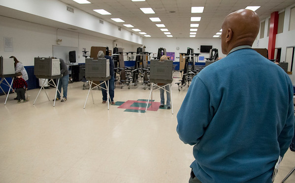 11/05/19 Wesley Bunnell | StaffrrVoters wait with their ballots for an empty voting booth at Slade Middle School on Tuesday evening.