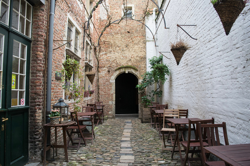 an alleyway with tables and chairs lining the walls
