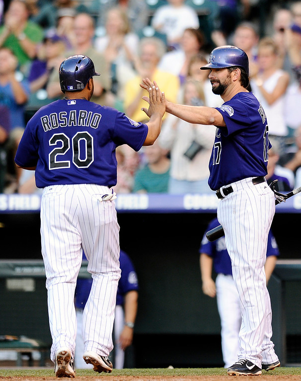 . Colorado Rockies Todd Helton, right, congratulates teammate Wilin Rosario, left, after both scored on a double by Tyler Chatwood  in the second inning of a baseball game against the Milwaukee Brewers, Friday, July 26, 2013, in Denver. (AP Photo/Chris Schneider)