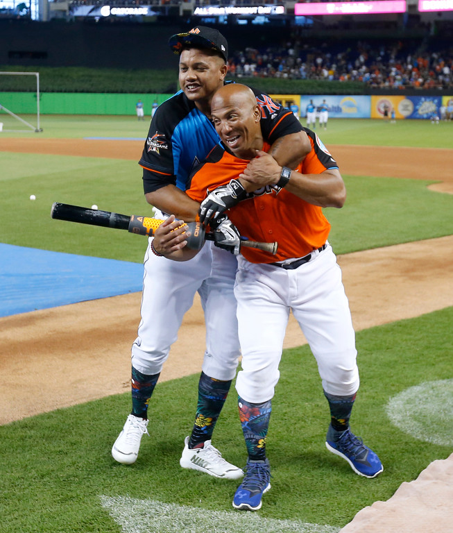 . New York Yankees\' Starlin Castro, behind, jokes with Chicago Cubs coach Franklin Font, foreground, before the MLB baseball All-Star Home Run Derby, Monday, July 10, 2017, in Miami. (AP Photo/Wilfredo Lee)