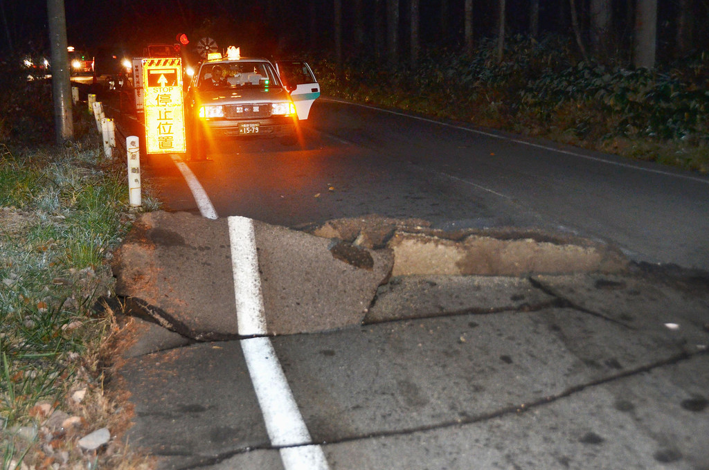 . A taxi stops by a crack on the road that leads to Hakuba from Nagano, Nagano Prefecture, after a strong earthquake hit central Japan, Saturday, Nov. 22, 2014. The magnitude-6.8 earthquake struck in the mountainous area of central Japan Saturday night. No tsunami warning was issued. (AP Photo/Kyodo News)
