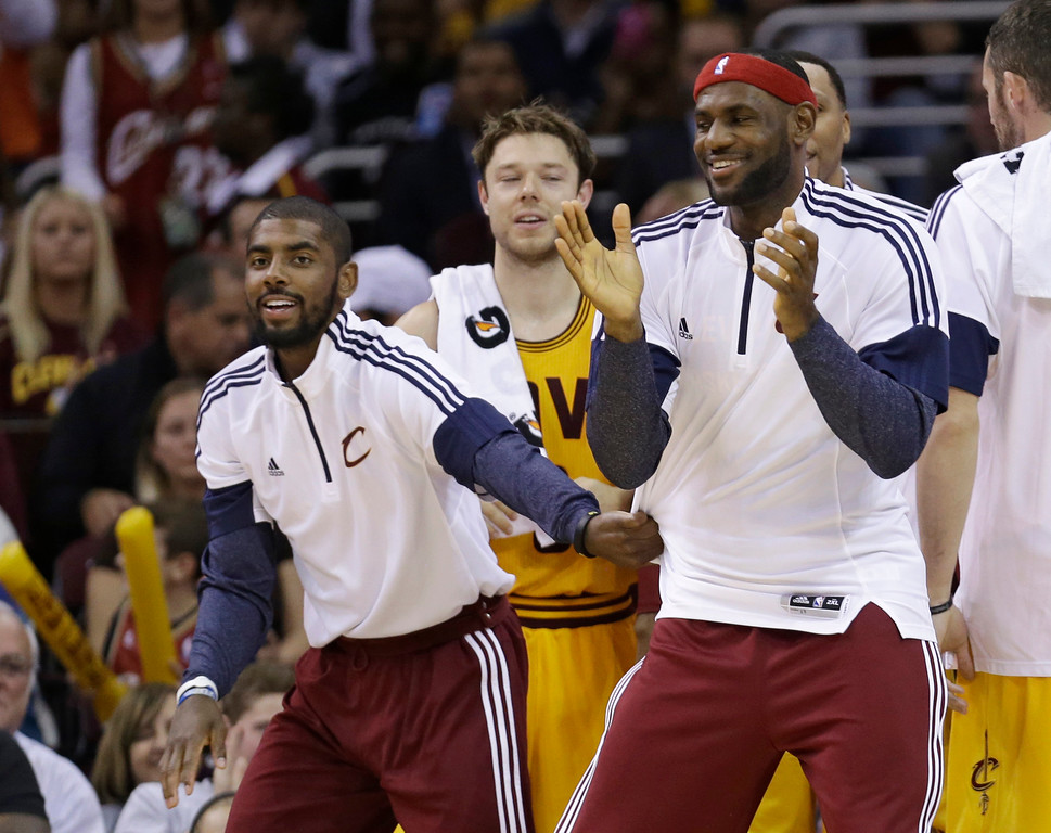 . Cleveland Cavaliers\' Kyrie Irving, left, and LeBron James cheer on teammates during the fourth quarter of an NBA preseason basketball game against the Milwaukee Bucks on Tuesday, Oct. 14, 2014, in Cleveland. The Cavaliers defeated the Bucks 106-100. (AP Photo/Tony Dejak)