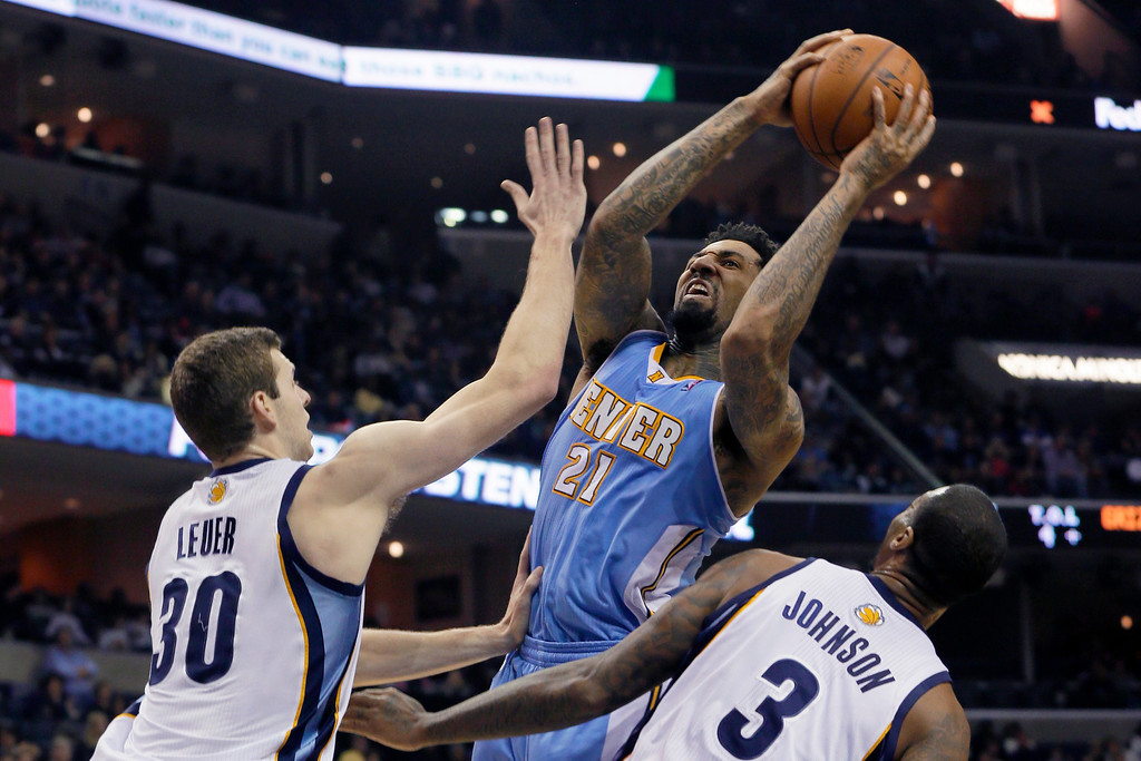 . Denver Nuggets\' Wilson Chandler (21) shoots over Memphis Grizzlies\' Jon Leuer (30) and James Johnson (3) during the first half of an NBA basketball game in Memphis, Tenn., Saturday, Dec. 28, 2013. (AP Photo/Danny Johnston)