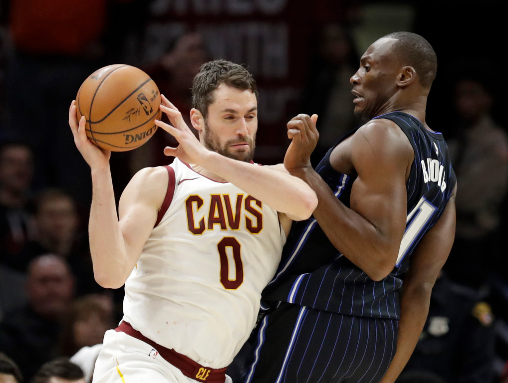 . Cleveland Cavaliers\' Kevin Love (0) drives past Orlando Magic\'s Jonathon Simmons (17) during the second half of an NBA basketball game Thursday, Jan. 18, 2018, in Cleveland. The Cavaliers won 104-103. (AP Photo/Tony Dejak)