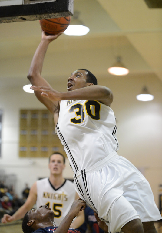 . Bishop Montgomery\'s Lamond Murray Jr., (30) puts up a shot against La Verne Lutheran\'s Joseph Rushing (35), but is called for charging, in a CIF SS Division IV-AA semifinal game in Torrance Friday night. Lutheran stunned Bishop Montgomery 63-59, ending their unbeaten season. 20130222 Photo by Steve McCrank / Staff Photographer