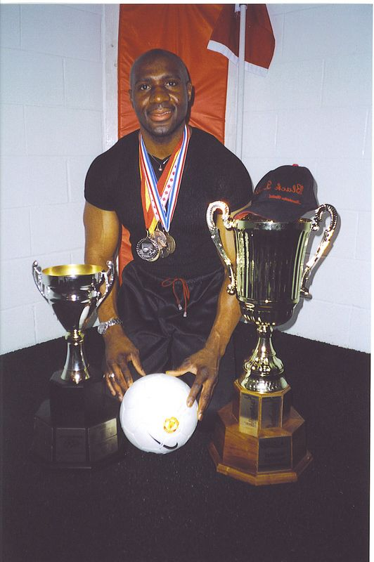 """""""THE HARDWARE"""" - BAS FEATURED MEMBER, Barry Mowatt, coach of UNITED BLACK DEVILS poses with the """"fruits of his labours""""."""