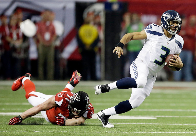 . Seattle Seahawks quarterback Russell Wilson (3) runs past Atlanta Falcons defensive end Kroy Biermann (71) during the first half of an NFC divisional playoff NFL football game Sunday, Jan. 13, 2013, in Atlanta. (AP Photo/David Goldman)