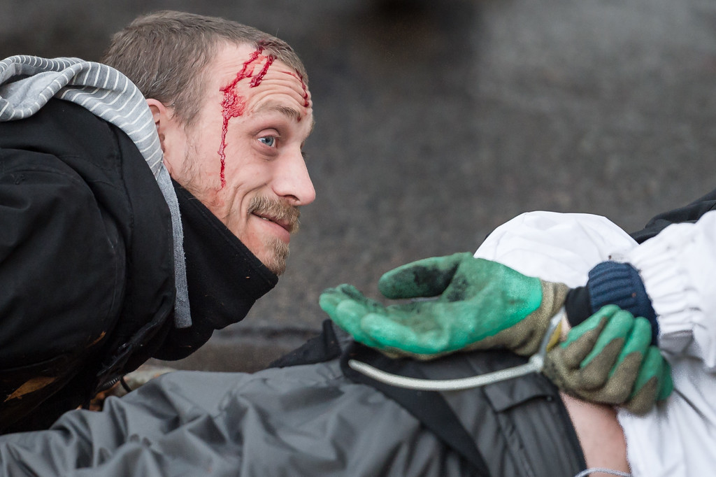 . An arrested protestor bleeds as he lays on the ground next to another arrested person during a national trade union demonstration in Brussels, Thursday Nov. 6, 2014.  (AP Photo/Geert Vanden Wijngaert)