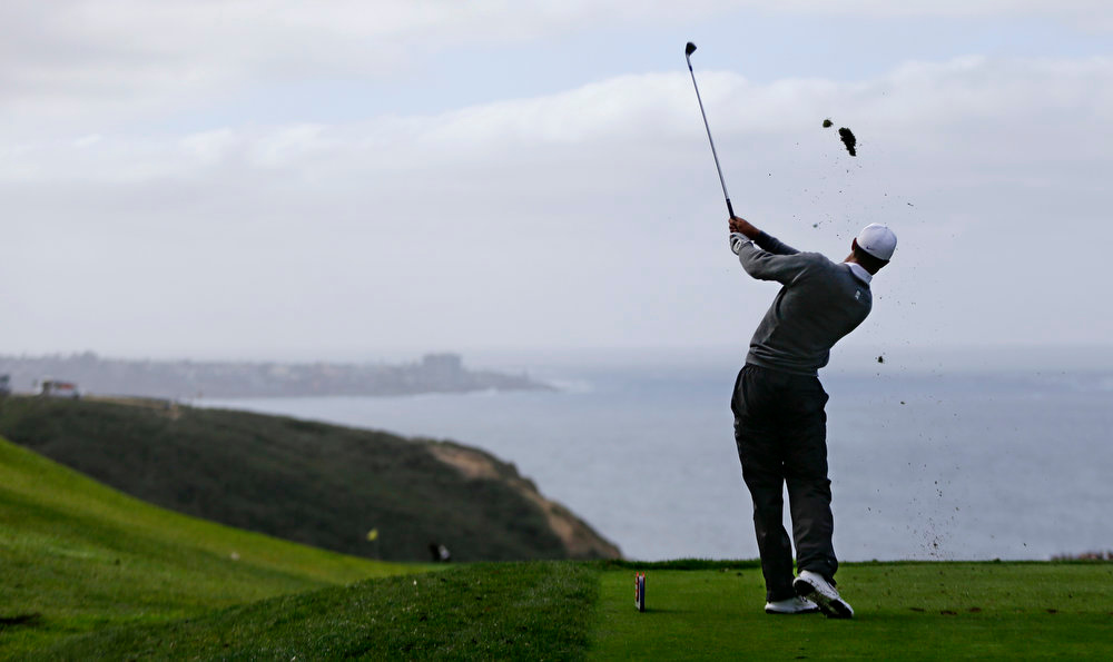 Description of . Tiger Woods hits his tee shot on the par three third hole on the South Course at Torrey Pines during the third round of the Farmers Insurance Open PGA golf tournament Sunday, Jan. 27, 2013, in San Diego. (AP Photo/Lenny Ignelzi)