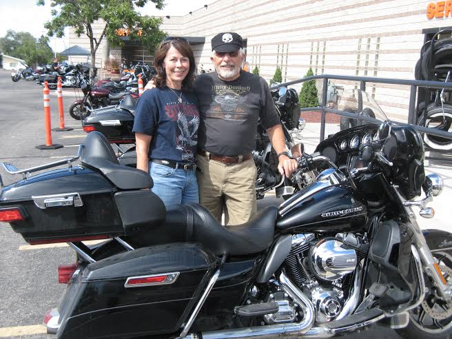 Two baby boomers standing behind a motorcycle