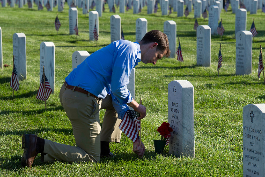 . Sen. Tom Cotton, R-Ark., places a flag at a headstone as members of the Army 3d U.S. Infantry Regiment, The Old Guard, honor the nation\'s fallen military heroes during its annual Flags In ceremony at Arlington National Cemetery,  Thursday, May 24, 2018, in Arlington, Va. Cotton, an Army veteran, was a member of The Old Guard. (AP Photo/Cliff Owen)