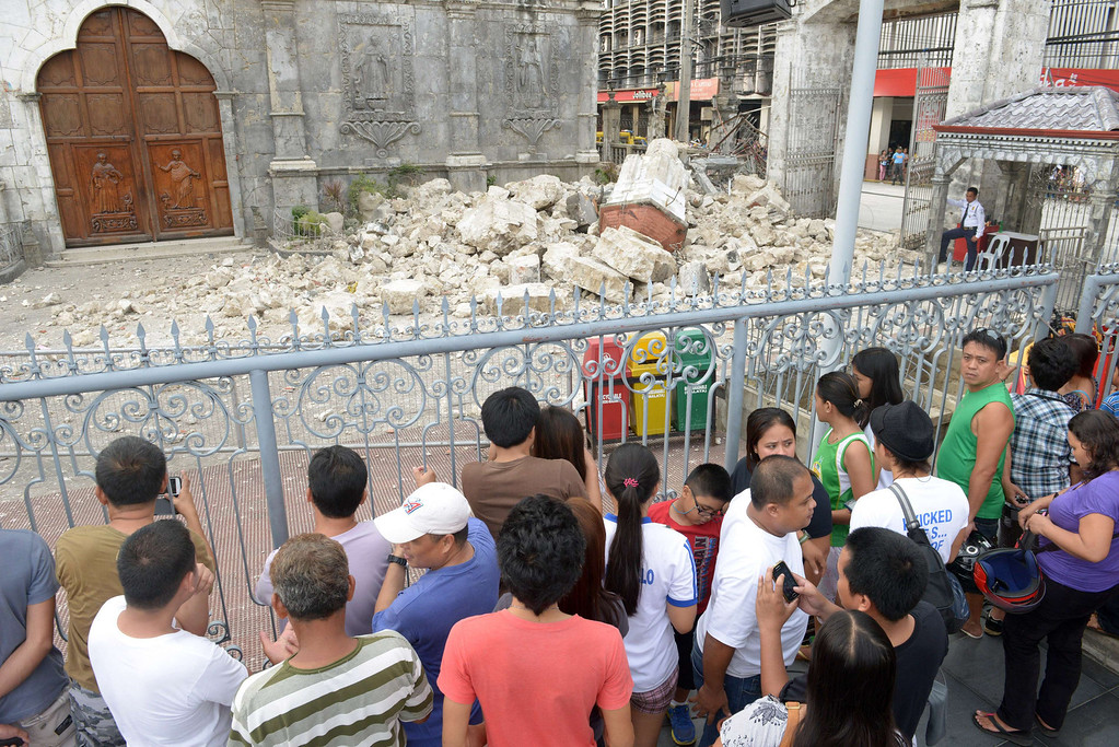 . People look at the ruins of Basilica Minore del Santo Nino bell tower following a 7.1-magnitude quake in Cebu on October 15, 2013.   AFP PHOTO / Jay  DIRECTO/AFP/Getty Images