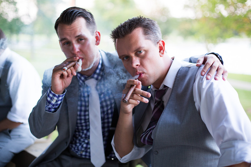 Groom and best man share cigars. Wedding reception at Lake Lawn Resort in Delavan, Wisconsin. Wedding photographer – Ryan Davis Photography – Rockford, Illinois.