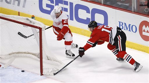 . Chicago Blackhawks center Jonathan Toews (19) is unable to score a wrap around goal as Detroit Red Wings left wing Tomas Tatar (21) watches during the second period of an NHL hockey game Wednesday, Feb. 18, 2015, in Chicago. (AP Photo/Charles Rex Arbogast)