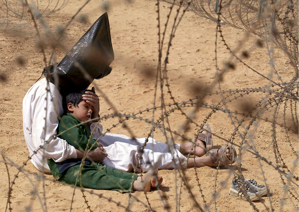 . An Iraqi prisoner of war comforts his 4-year-old son at a regroupment center for POWs of the 101st Airborne Division near An Najaf, March 31, 2003. The man was seized in An Najaf with his son, and the U.S. military did not want to separate them. (AP Photo/Jean-Marc Bouju)