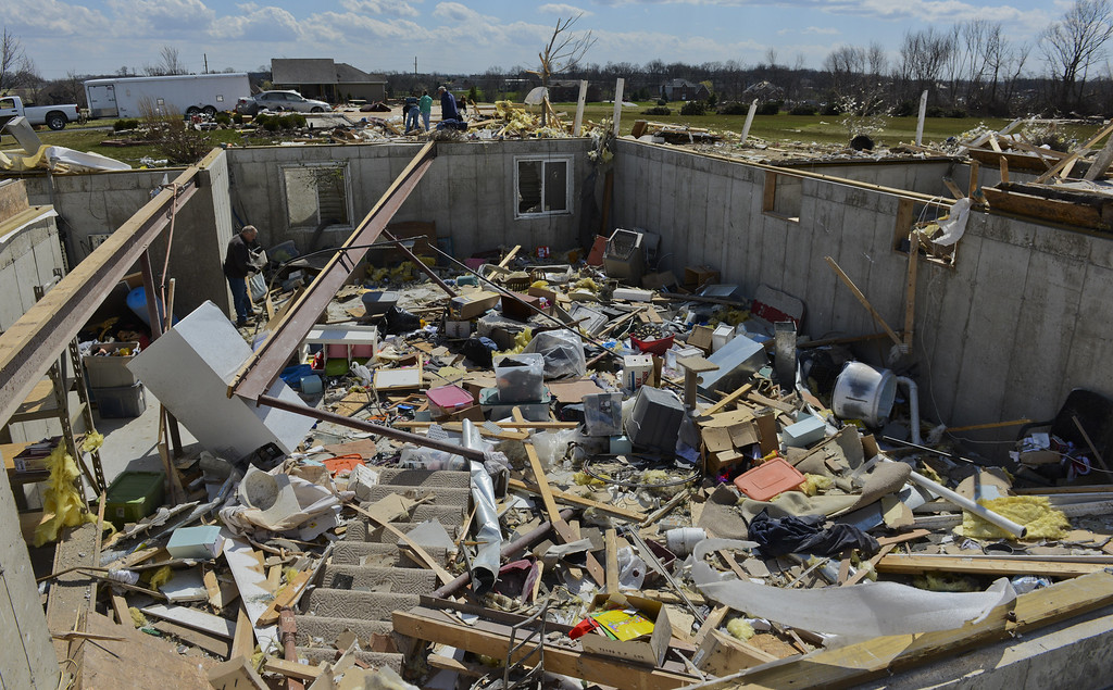 . Terry Dickow helps clean out John Whitaker\'s home in the Cherry Hill subdivision outside of Flagg Center, Ill., on Friday, April 10, 2015.  The National Weather Service says at least two tornadoes churned through six north-central Illinois counties. (AP Photo/Matt Marton)