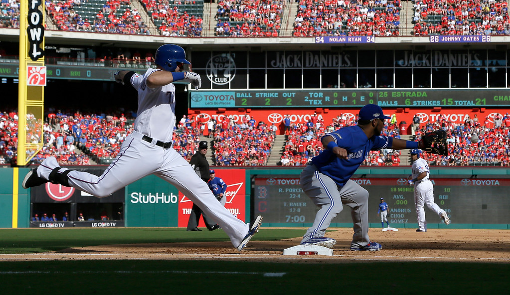 . Texas Rangers\' Mitch Moreland, left, is unable able to beat the throw to Toronto Blue Jays first baseman Edwin Encarnacion on a groundout to second in the second inning of baseball Game 1 of the American League Division Series, Thursday, Oct. 6, 2016, in Arlington, Texas. (AP Photo/David J. Phillip)