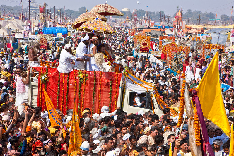 Parade. Vaisnava, the follower of Lord Vishnu parade through Mela grounds singing Bhajan (devotional song) to their destination akhara. during Kumbha Mela in Allahabad. Gurus or head of Akhara ride flower decked vehicle under umbrella, waving as gesture of blessings while his followers walk surrounding his vehicle carrying holy flags that connote their sect. India.