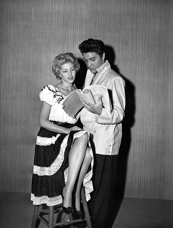 ". Singer-actor Elvis Presley, right, and co-star and companion Anne Neyland of Texas read over the script of the musical movie ""Jailhouse Rock\"" at MGM studios in Hollywood, Ca., June 6, 1957.  (AP Photo)"