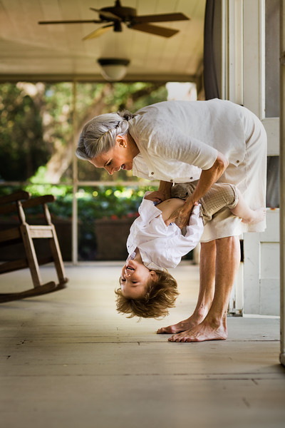 Grandmother holding grandson upside down.