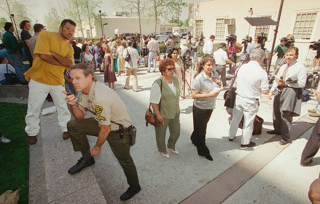 . File - Ed Elder, a Los Angeles County Sheriff deputy, stands guard outside Los Angeles County Courthouse on Wednesday, March 20, 1996 in the Van Nuys section of Los Angeles, as spectators and media converge on the building after a jury convicted Erik and Lyle Menendez of first degree murder for killing their parents. (AP Photo/Kevork Djansezian)