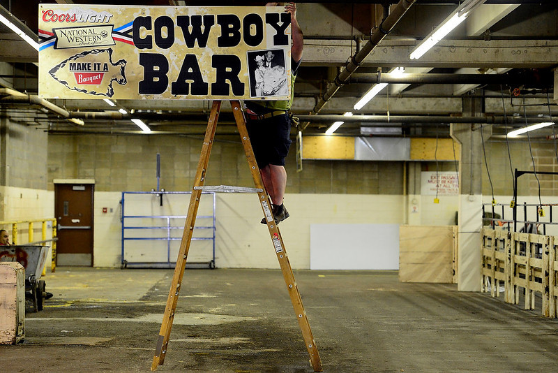 . Jasper Van Wyk, of Coors, hangs a banner in preparation for the National Western Stock Show at the complex on Wednesday, January 9, 2012. AAron Ontiveroz, The Denver Post