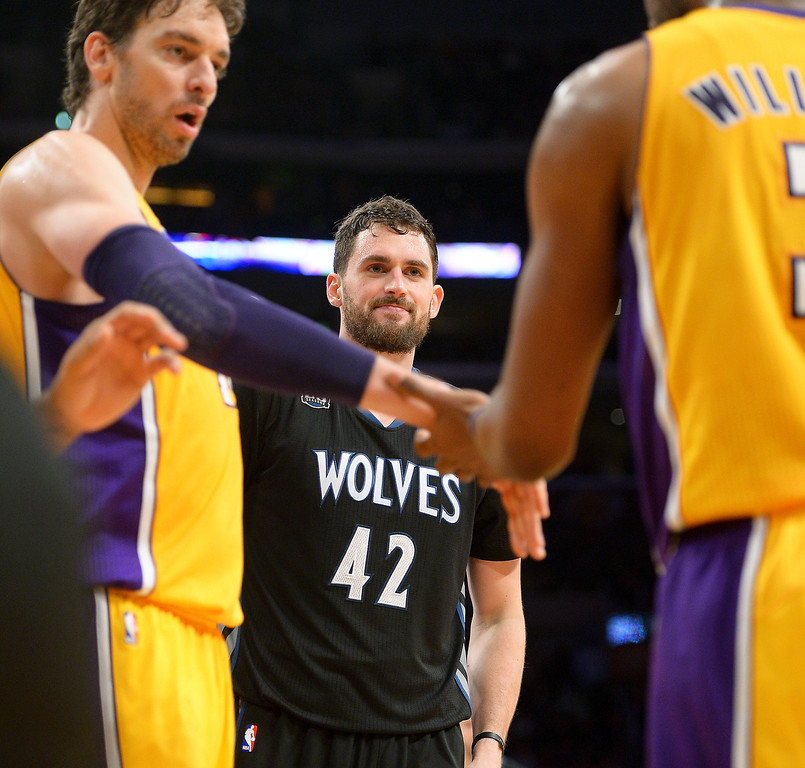 . The Timberwolves\' Kevin Love watches as the Lakers\' Pau Gasol congratulates Shawne Williams for a block, Friday, December 20, 2013, at Staples Center. (Photo by Michael Owen Baker/L.A. Daily News)