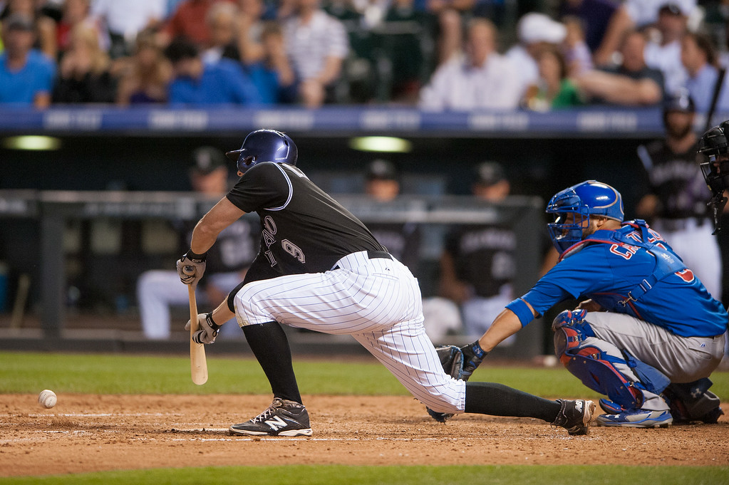 . DENVER, CO - AUGUST 06:  DJ LeMahieu #9 of the Colorado Rockies lays down a suicide squeeze bunt single for an RBI in the sixth inning of a game against the Chicago Cubs at Coors Field on August 6, 2014 in Denver, Colorado.  (Photo by Dustin Bradford/Getty Images)