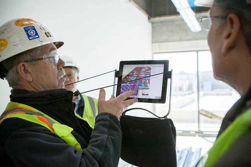 . On the tour, faculty see the inner workings of the building on an interactive tablet. The thermal science labs won\'t have ceilings so everything can be exposed, allowing students to see all the systems. (Photo by Jason Willis/Oakland University)
