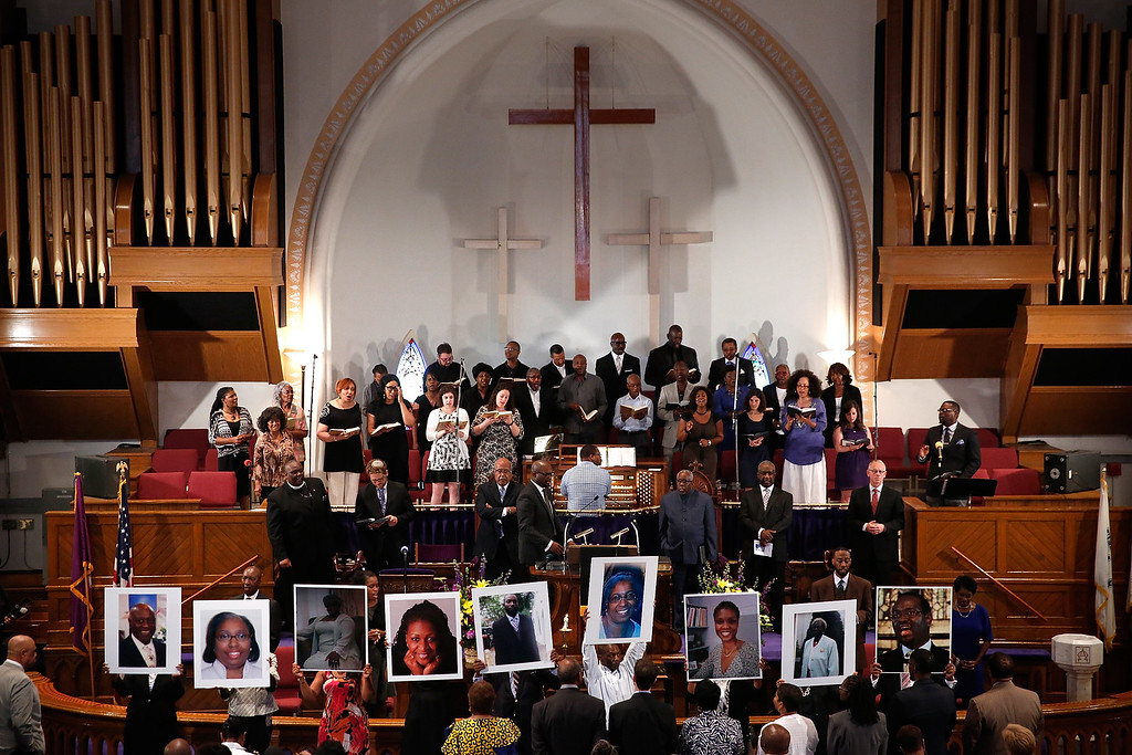 . Photographs of the nine victims killed at the Emanuel African Methodist Episcopal Church in Charleston, South Carolina are held up by congregants during a prayer vigil at the the Metropolitan AME Church June 19, 2015 in Washington, DC. Earlier today the suspect in the case, Dylan Storm Roof, was charged with nine counts of murder.  (Photo by Win McNamee/Getty Images)