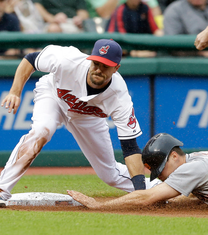 . Cleveland Indians\' Lonnie Chisenhall, top, tags out Detroit Tigers\' Don Kelly after Kelly tried to steal third base in the third inning of a baseball game on Friday, June 20, 2014, in Cleveland. (AP Photo/Tony Dejak)