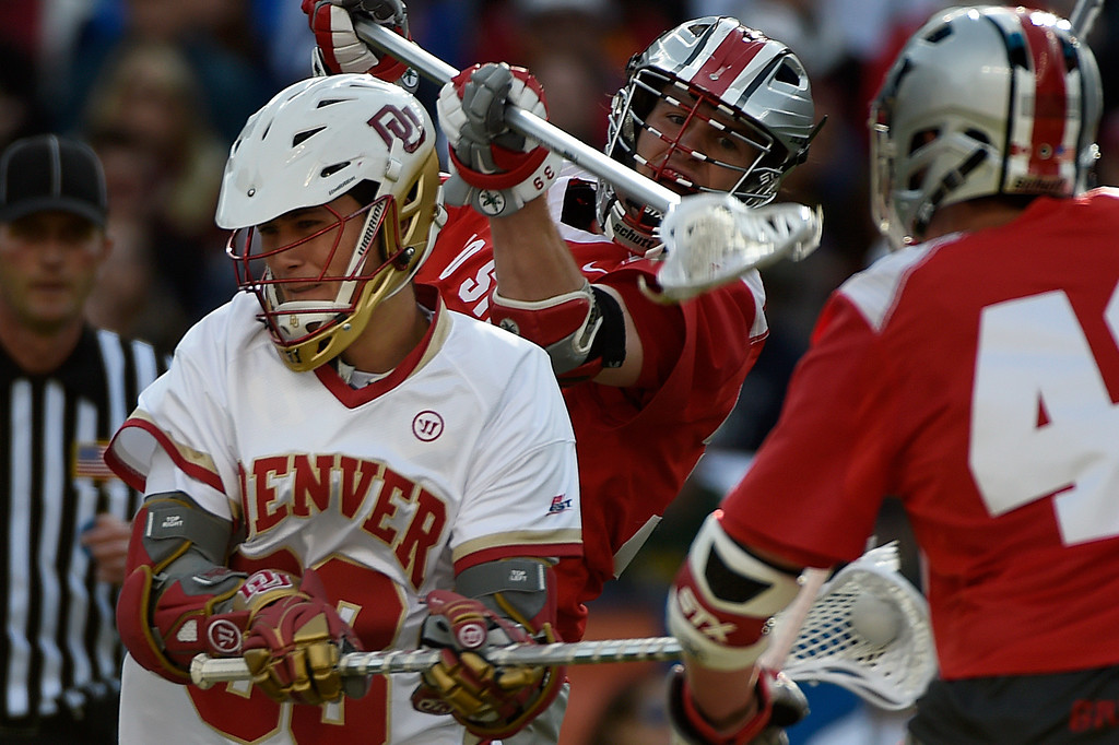 . Zach Miller (33) of the Denver Pioneers is defended by  Evan Mulchrone (39) of the Ohio State Buckeyes and  Erik Evans (43) of the Ohio State Buckeyes during the first half of their NCAA tournament quarterfinal match. The Denver Pioneers played the Ohio State Buckeyes at Sports Authority field at Mile High on Saturday, May 16, 2015. (Photo by AAron Ontiveroz/The Denver Post)