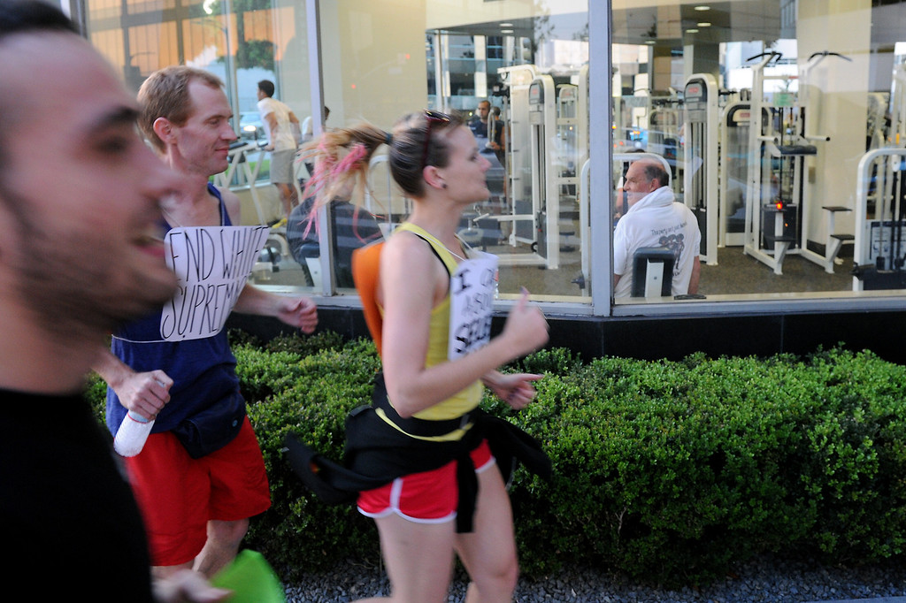 """. Protesters jog past a gym in Westwood during a \""""Smash White Supremacy Fun Run,\"""" Thursday, July 18, 2013. (Michael Owen Baker/L.A. Daily News)"""