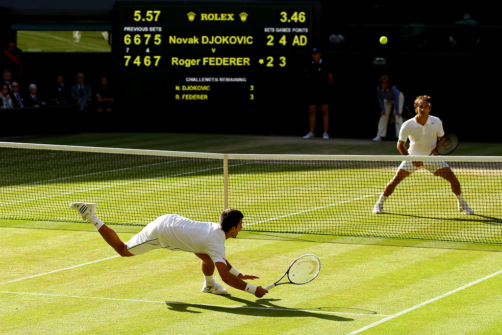 . Novak Djokovic of Serbia dives to make a return as Roger Federer of Switzerland stands at the net during the Gentlemen\'s Singles Final match on day thirteen of the Wimbledon Lawn Tennis Championships at the All England Lawn Tennis and Croquet Club on July 6, 2014 in London, England.  (Photo by Al Bello/Getty Images)