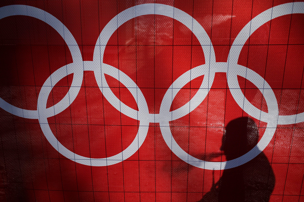 . The shadow of a man is cast on the Olympic rings as he smokes at the Rosa Khutor Alpine Center, at the 2014 Winter Olympics, Saturday, Feb. 15, 2014, in Krasnaya Polyana, Russia. (AP Photo/Andy Wong)